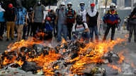 Opposition supporters stand in front of a fire during clashes with riot police at a rally against President Nicolas Maduro in Caracas, Venezuela, May 3, 2017.