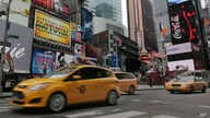 FILE — New York City taxis pass through New York's Times Square.