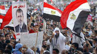 Supporters of Muslim brotherhood's presidential candidate Mohamed Morsi wave Egypt's national flag and posters of him in Tahrir Square in Cairo, June 19, 2012.
