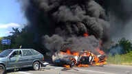 Two police cars ablaze at the site of unrest in Mukhachevo, Western Ukraine, July 11, 2015.