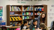 Chelsea Duvenez, upper right, works with students in her fourth-grade classroom at Olympic View Elementary School, Friday, March 9, 2018, in Lacey, Wash. (AP Photo/Ted S. Warren)