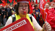 """A supporter of the Confederation of German Trade Unions (DGB) blows a whistle as she takes part in a union rally for """"political change"""" in Frankfurt, Sept. 7, 2013."""