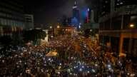 Tens of thousands of pro-democracy demonstrators, some waving lights from mobile phones, fill the streets in the main finical district of Hong Kong, Wednesday, Oct. 1, 2014.
