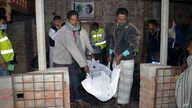 Bangladeshi men remove the body of a suspected suicide bomber after an explosion was touched off at a mosque of a minority Ahmadiya Muslim sect, in Bagmara, Rajsahi district, Bangladesh, Dec. 25, 2015.
