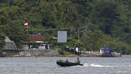 FILE - Indonesian military patrol in a small inflatable boat near a ferry boat dock on the prison island of Nusakambangan, in the background, in Central Java. March 3, 2015. Abdurrahman is being held at Nusakambangan, a maximum-security facility..