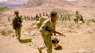 FILE - An Eritrean soldier carries his rifle and teapot as the Eritrean army begins to pull out from the frontline near Senafe on Feb. 17, 2001.