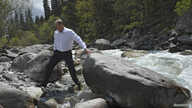 FILE - During a visit to Krygyzstan, Russia's President Vladimir Putin crosses a stream in Ala-Archa National Park, south of Bishkek, May 28, 2013.