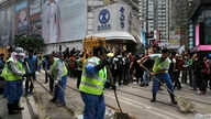 Workers sweep after police cleared barricades and tents on a main road in the occupied areas at Causeway Bay district in Hong Kong, Dec 15, 2014.