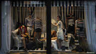 FILE - A shop assistant arranges summer clothes in a shop window in the Myeong-dong shopping district in Seoul.