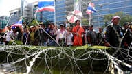 Anti-government protesters chant slogans during a rally outside the office of the permanent secretary for defense where Prime Minister Yingluck Shinawatra was reportedly working inside, Monday, Feb. 3, 2014.