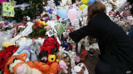 A woman puts a photo of a child on a makeshift memorial in the Sandy Hook Village of Newtown, Conn., as the town mourns victims killed in a school shooting, Dec. 17, 2012.