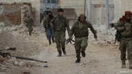 A rebel fighter runs with a weapon on the outskirts of the northern Syrian town of al-Bab, Syria, Jan. 26, 2017.