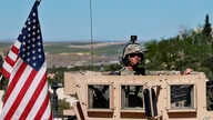 ILE - In this April 4, 2018 file photo, a U.S. soldier sits on his armored vehicle on a road leading to the tense front line  in Manbij, Syria.