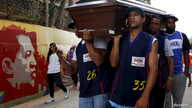 FILE - Relatives and basketball teammates of a crime victim carry his coffin prior to his burial in Caracas, Venezuela, Nov. 25, 2015.