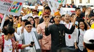 Indonesian President Joko Widodo, center right, walks and his running mate Ma'ruf Amin during a ceremony marking the kick off of the campaign period for next year's election in Jakarta, Sept. 23, 2018.