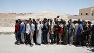 FILE - A group of alleged Islamic State members, pardoned by the Civil Council of Raqqa, are seen during an earlier pardoning ceremony in Ain Issa village, north of Raqqa, Syria, June 24, 2017.