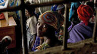 A Congolese woman refugee sits with others at the Nkamira