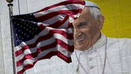 The U.S. flag flies in front of a mural of Pope Francis on the side of a building in midtown Manhattan in New York, Aug. 28, 2015.