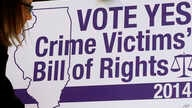 FILE - Reporters gather at a news conference on the Crime Victims' Bill of Rights, also known as Marsy's Law for Illinois, in Springfield, Ill., Oct. 15, 2014.