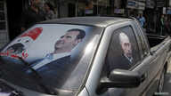 FILE - A poster of Syria's President Bashar al-Assad and a photo of Russian President Vladimir Putin (R) are seen on a car near Latakia, Syria, May 26, 2014.