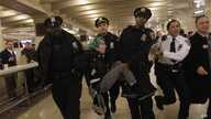 Occupy Wall Street activist Lauren Digioia is detained by police during a demonstration against the National Defense Authorization Act in New York's Grand Central Station, Jan. 3, 2012.