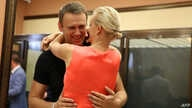 Russia's top opposition leader Alexei Navalny hugs his wife Yulia in the courtroom in Kirov, July 19, 2013.