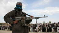 A member of the Taliban stands with others at the execution of three men in Ghazni Province, April 18, 2015. Residents of the area say Islamic State has threatened them to stop supporting the Taliban and support Islamic State instead.