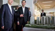 Zhang Dejiang, left, chairman of China's National People's Congress, and Hong Kong Chief Executive Leung Chun-ying, right, look at a model of newly built public housing blocks due to open later this year in Hong Kong on May 19, 2016.