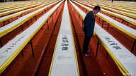 FILE - A visitor looks at a part of a Chinese calligraphy of Buddhist scriptures done by artist He Guojian on display at a stadium in Shenzhen, Guangdong province.