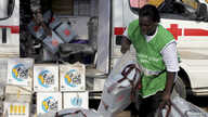 A local health worker carries vaccination kits into a vehicle at a distribution center ahead of the start of a nationwide polio immunization campaign in Lagos, Nigeria, February 21, 2011.