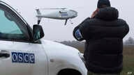 A member of the Organization for Security and Co-operation in Europe (OSCE) mission to Ukraine watches a drone take off during a test flight near the town of Mariupol, eastern Ukraine, Oct. 23, 2014.