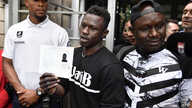 Malian migrant Mamoudou Gassama (C) flanked by his older brother (R) holds his temporary residence permit after receiving it at the Prefecture of Bobigny, northeast of Paris, on May 29, 2018.