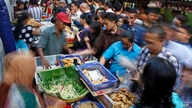 """Office workers shop for """"iftar,"""" the meal to break their fast on the first day of the holy fasting month of Ramadan, at the main business district in Jakarta, Indonesia, June 18, 2015."""