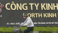 FILE - A man rides a bicycle past a Kinh Do factory in Vietnam's northern Hung Yen province, outside Hanoi.