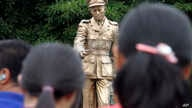 FILE - People stand in front of a statue of Gen. Aung San, late father of Myanmar National League for Democracy leader Aung San Suu Kyi, during a ceremony at a park in Yangon, Myanmar, July 19, 2015.