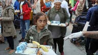 FILE - Child carries a tray of food during birthday party at refugee camp in Traiskirchen, Austria, Sept. 9, 2015.