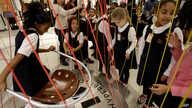 FILE - Girls from a city preparatory school play with an interactive exhibit at the National Museum of Mathematics in New York.