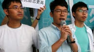 Newly elected lawmaker Nathan Law (C), student leaders Joshua Wong (R) and Alex Chow meet journalists outside a court before a hearing as prosecutors asked them to be jailed immediately over their roles in storming government headquarters in 2014 whi...