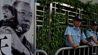 Police officers stand guards next to a portrait of jailed Chinese Nobel Peace laureate Liu Xiaobo during a demonstration outside the Chinese liaison office in Hong Kong, July 10, 2017.
