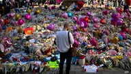 A man stands next to flowers for the victims of Monday's bombing at St Ann's Square in central Manchester, England, May 26 2017.