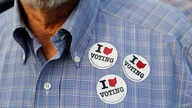FILE - A man wears stickers after casting his ballot at the Hamilton County Board of Elections in Cincinnati, Oct. 10, 2018. In addition to choosing candidates, voters are deciding ballot initiatives.
