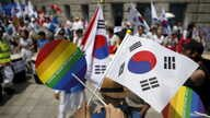 An activist holds up a rainbow-colored fan and a South Korean national flag as gay pride festival participants face Christians opposed to homosexuality in central Seoul, South Korea, June 28, 2015.