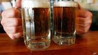 FILE - A bartender serves two mugs of beer at a tavern in Montpelier, Vermont, June 29, 2004.