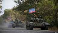 FILE - Russia-backed rebel tanks with a flag of the self-proclaimed Donetsk People's Republic are seen near Novoazovsk, eastern Ukraine, Oct.  21, 2015.