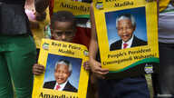A boy holds a poster with an image of former South African President Nelson Mandela near Qunu, Dec. 13, 2013.