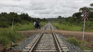 A man rides a bike over a railway line in Moatize in Tete province February 13, 2013. The Renamo opposition party is threatening to paralyze the Mozambique railway that transports coal to the coast for export.