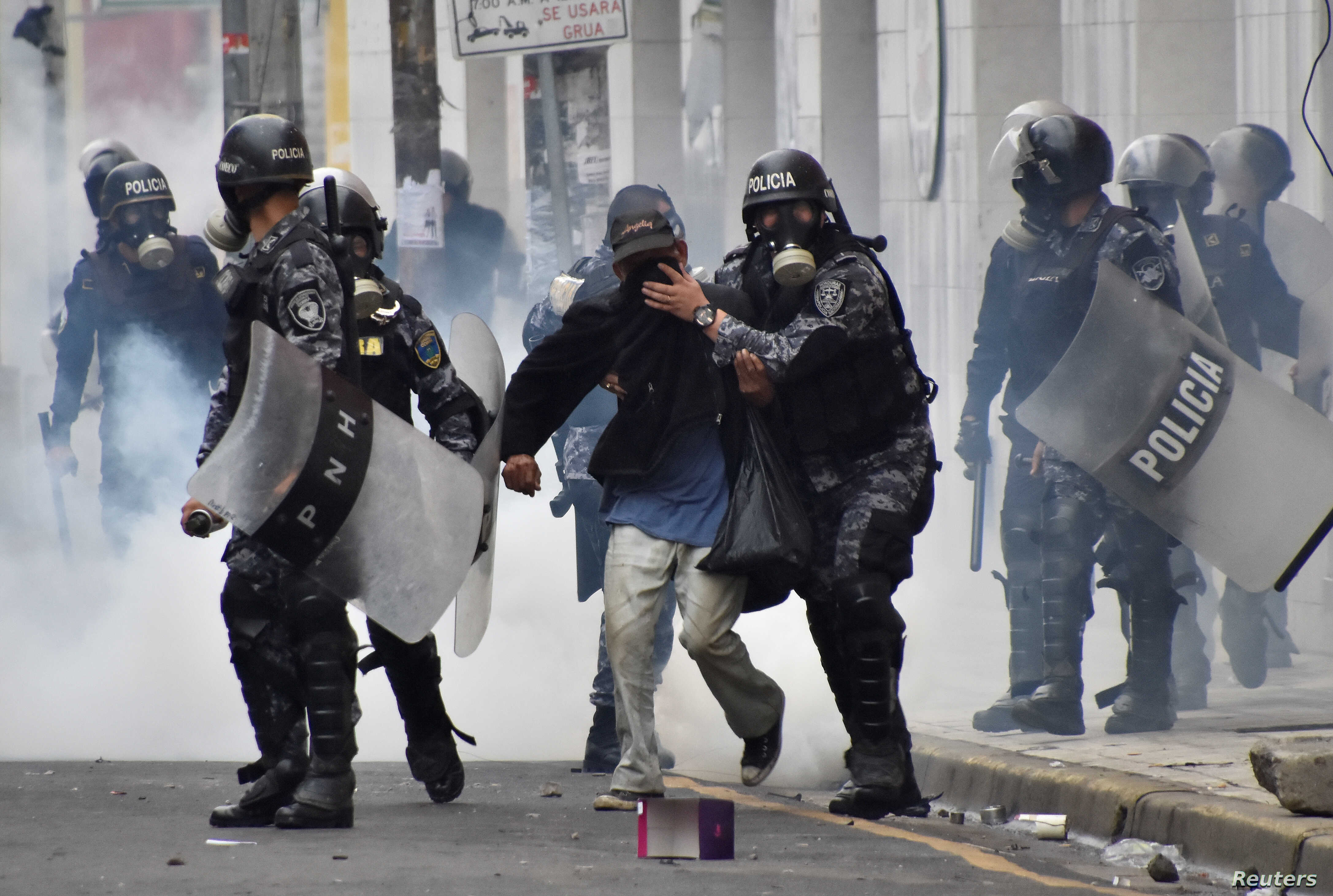 Police help a pedestrian overcome by tear gas as supporters of Salvador Nasralla, presidential candidate for the Opposition Alliance Against the Dictatorship, clash with police during a protest caused by the delayed vote count for the presidential el