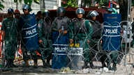 Cambodian riot police officers stand guard behind barbed wire as they block entry to Freedom Park, in Phnom Penh, Cambodia,  July 15, 2014.