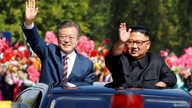 South Korean President Moon Jae-in and North Korean leader Kim Jong Un wave during a car parade in Pyongyang, North Korea, Sept. 18, 2018.