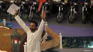"Aamir Liaquat Hussain, host of the Geo TV channel program ""Amaan Ramazan"", gestures while asking participants questions during a live show in Karachi, July 26, 2013."